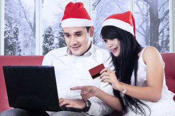 Couple paying online in christmas day