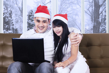 Couple with santa hat and laptop on sofa