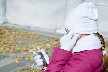 Girl child adjusts earphones talk on mobile