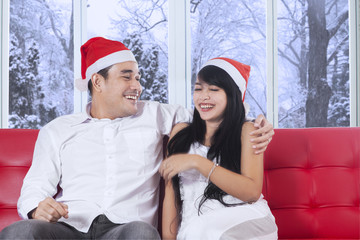 Happy couple in christmas hat laughing