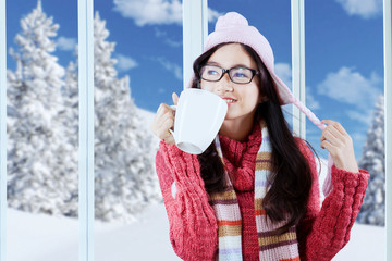 Happy girl in winter clothes enjoy hot drink