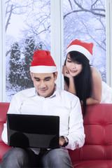 Hispanic couple in santa hat using laptop