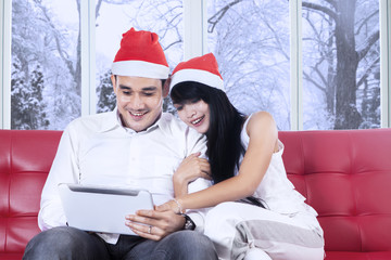 Hispanic couple in santa hat using tablet