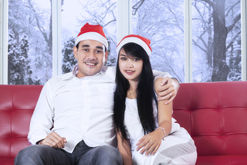Man with santa hat embrace his girlfriend