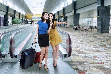 Two women carrying luggage in airport