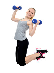 Happy healthy active girl jumps with dumbbells