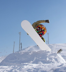 Snowboarder jumping against blue sky background