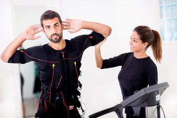 Female coach giving man ems electro muscular stimulation exerci