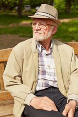 Alter Mann sitzt auf Bank im Park