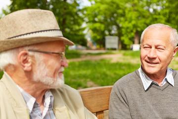 Zwei Senioren reden auf Bank im Pflegeheim miteinander