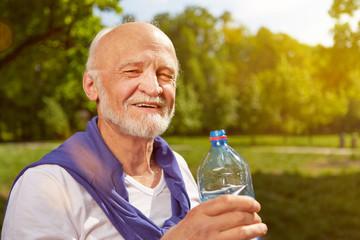 Durstiger Senior trinkt Wasser im Sommer