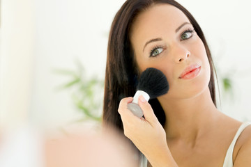 beautiful young woman applying Make-up with Cosmetics Brush