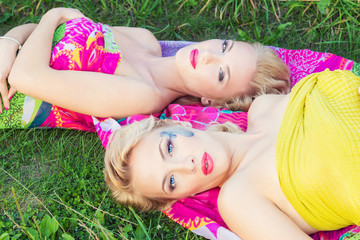 girls sisters with makeup lie on a bright blanket in a Park