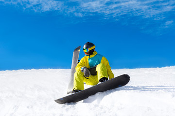 snowboarder sitting on snow mountain slope