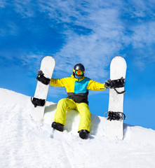 snowboarder hold two snowboards sitting on snow
