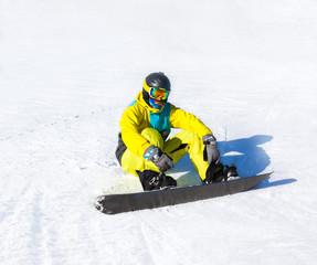 Snowboarder sitting on snow mountains