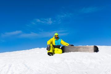 snowboarder sitting on snow mountain slope