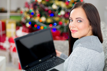 young smiling woman using laptop on Christmas Eve