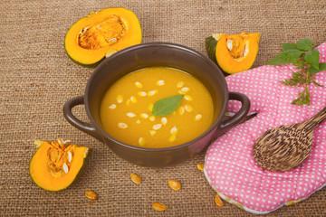Pumpkin soup in clay pot with fresh pumpkins