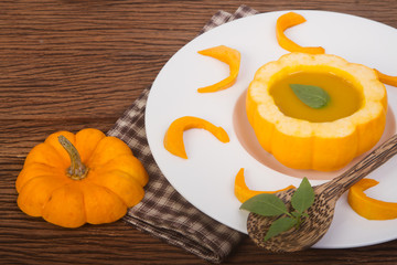 Pumpkin soup in a small pumpkin with herb leaf decoration in dis