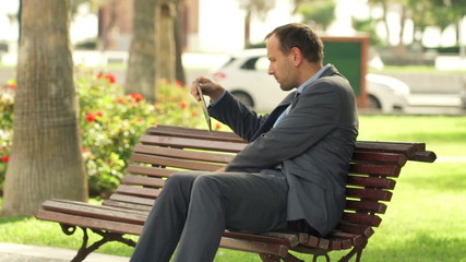 Businessman working on modern tablet computer, laptop on bench i