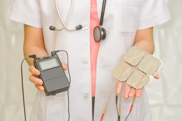 Doctor's hold Medical Tens Unit for pain therapy
