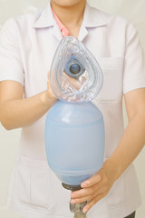 Doctor's hand holds breathing bag with face mask for help patien