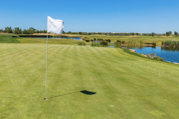 Golf course. Flag from the hole in the foreground.