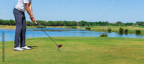Man simulates play golf. With the stick on the green field. - 72856752