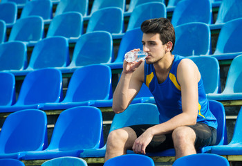 Tired man sitting on stadium and drinking mineral water