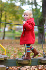 Happy little girl in red coat playing in the park