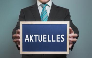 """Businessmann hät Holz-Tafel mit Text """"Aktuelles"""""""