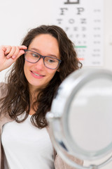 Young attractive woman trying new glasses