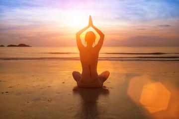 Silhouette yoga woman on sea coast at sunset.