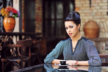 Beautiful girl drinking tea or coffee in cafe