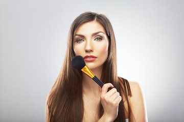 Portrait of young beautiful woman. Make up brush. Isolated