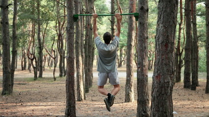 Workout pull-ups in pine forest