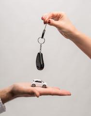 Man holding small car, woman holding car key