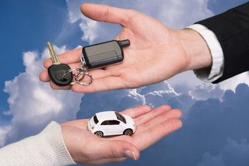 Man holding small car key, woman holding small car
