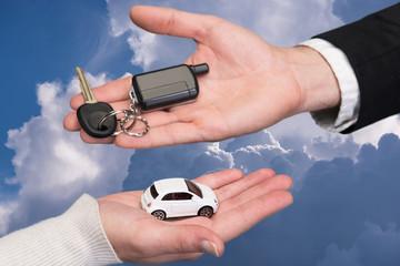 Man holding small car key, woman holding small car