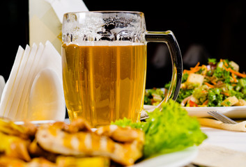 Mug of Beer on Restaurant Table with Plated Food