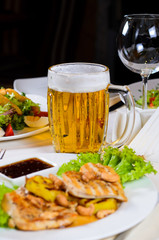 Mug of Beer Amidst Plated Dishes on Table