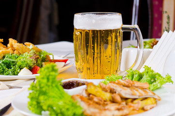 Mug of Beer on Table with Plated Food Dishes