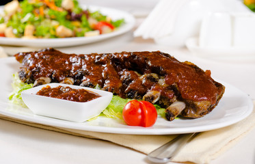 Plate of Saucy Barbecue Pork Ribs in Restaurant