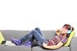 Young woman listening music on headphones and lying on a couch