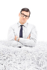 Sad man in a pile of shredded paper