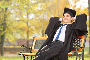 Relaxed graduate student sitting on a bench