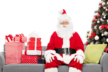 Santa sitting on a sofa by a Christmas tree