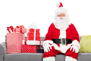 Santa sitting on a sofa full of Christmas presents