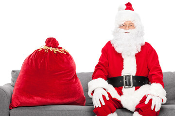 Santa sitting on a sofa with a bag full of presents next to him
